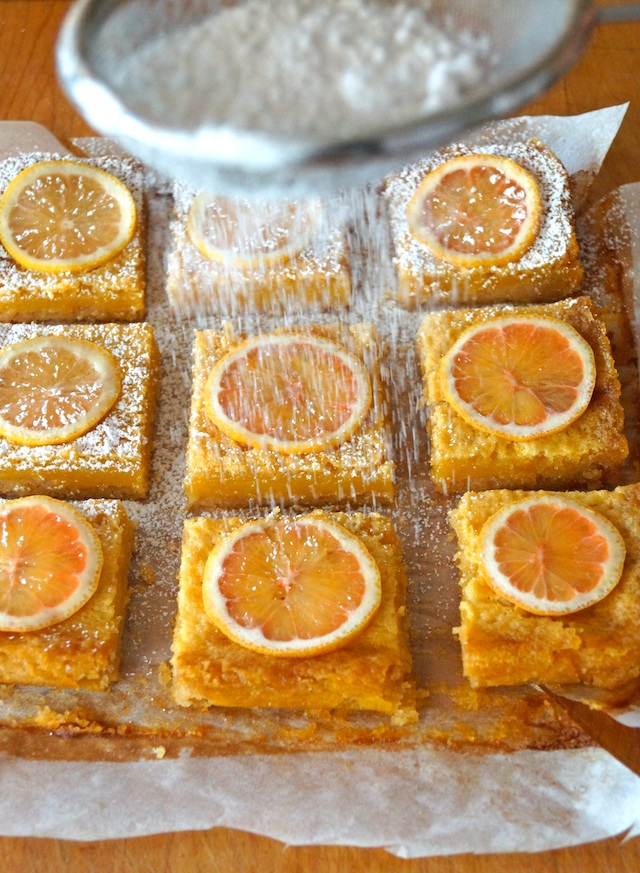 Gluten-Free Pink Lemonade-Coconut Bars cut into squares with a lemon slice on each one, with powdered sugar being sifted on top.