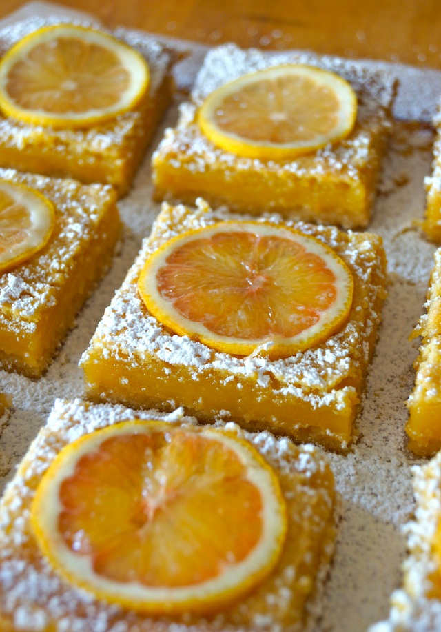 close up of a few Gluten-Free Lemon Bars with Coconut Crust on parchment.