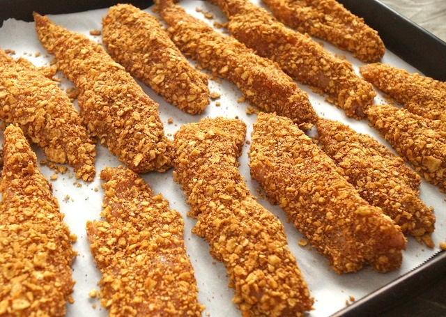 Spiced Tortilla Crusted Baked Chicken Strips on parchment paper on baking sheet