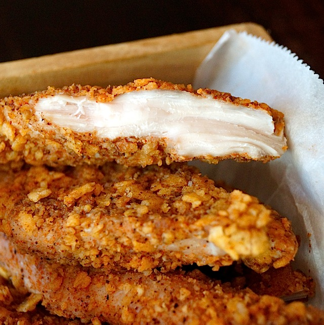 Small pile of Spiced Tortilla Chip Crusted Chicken Strips on parchment