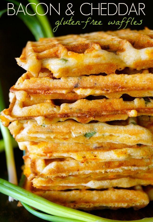 A huge stack of Bacon Cheddar Gluten-Free Waffles with a black background with a few green onions.