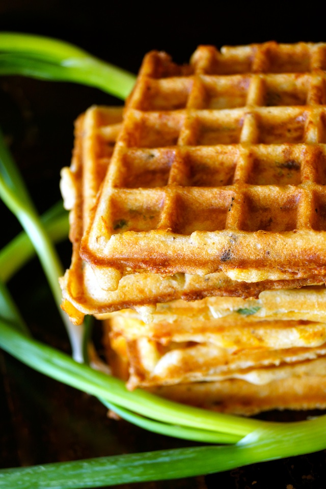 A small stack of Bacon Cheddar Gluten-Free Waffles with several whole, green scallions.