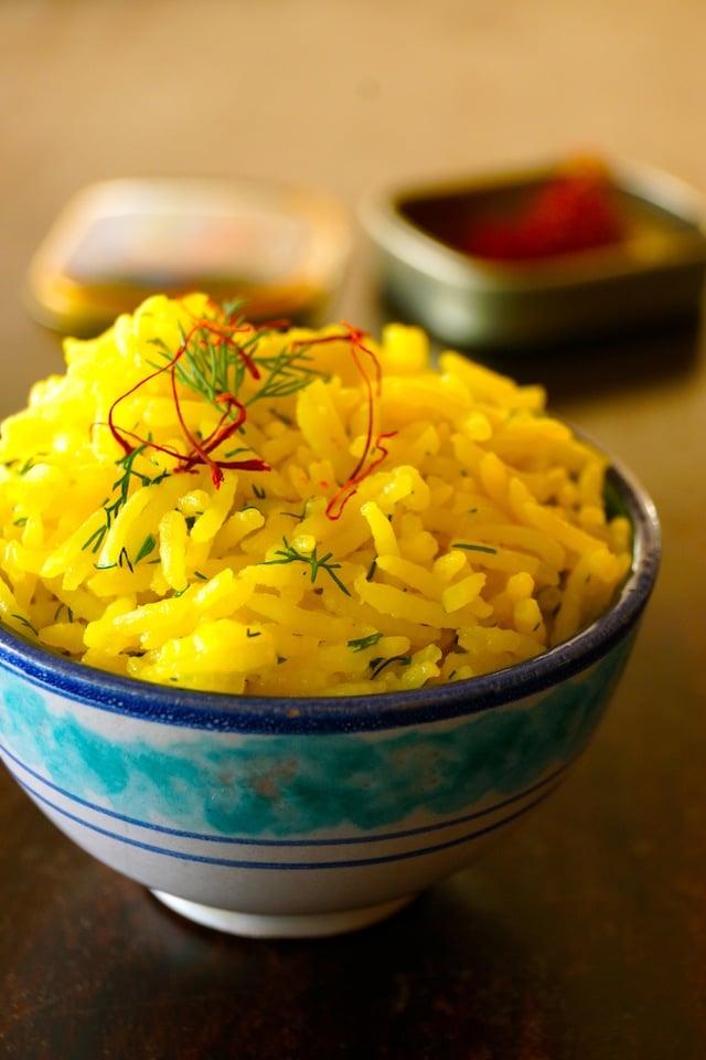Close up of Saffron Basmati Rice Recipe with Fresh Dill in a pretty blue and white ceramic bowl.