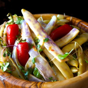 Dragon Tongue bean Salad with Honey Mustard Dressing in a wooden bowl with microgreens