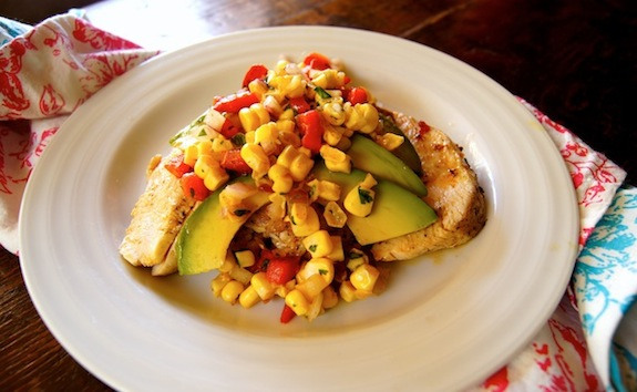 Grilled Chipotle Chicken with-Roasted Pepper Corn Relish on a white plate with avocado slices on top.