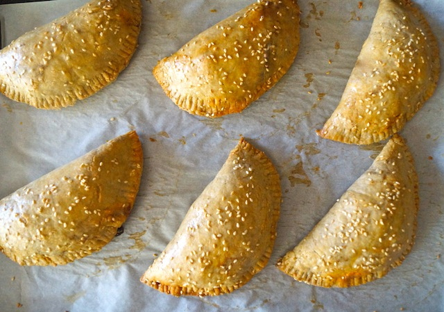Baked Chorizo-Potato Spiced Sesame Hand Pies on parchment paper
