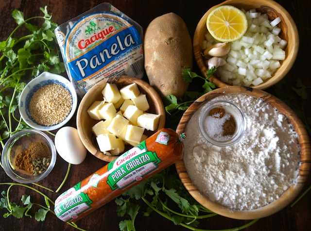 All of the ingredients for Chorizo-Potato Spiced Sesame Hand Pies on a dark board and with lots of fresh cilantro throughtout.