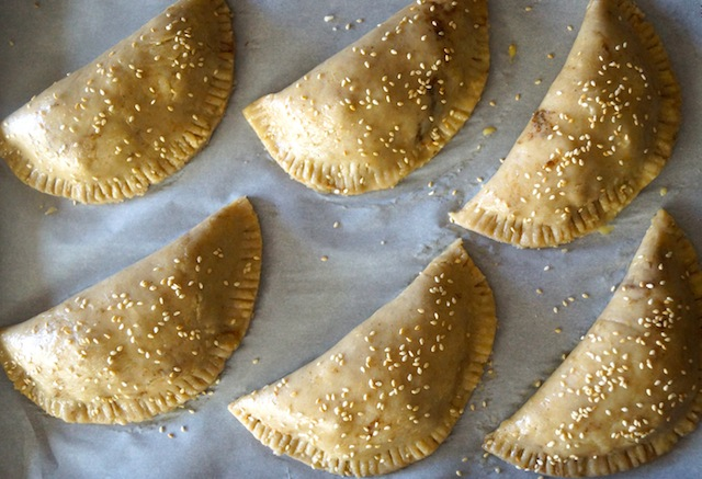 raw Chorizo-Potato Spiced Sesame Hand Pies on parchment with sesame seeds