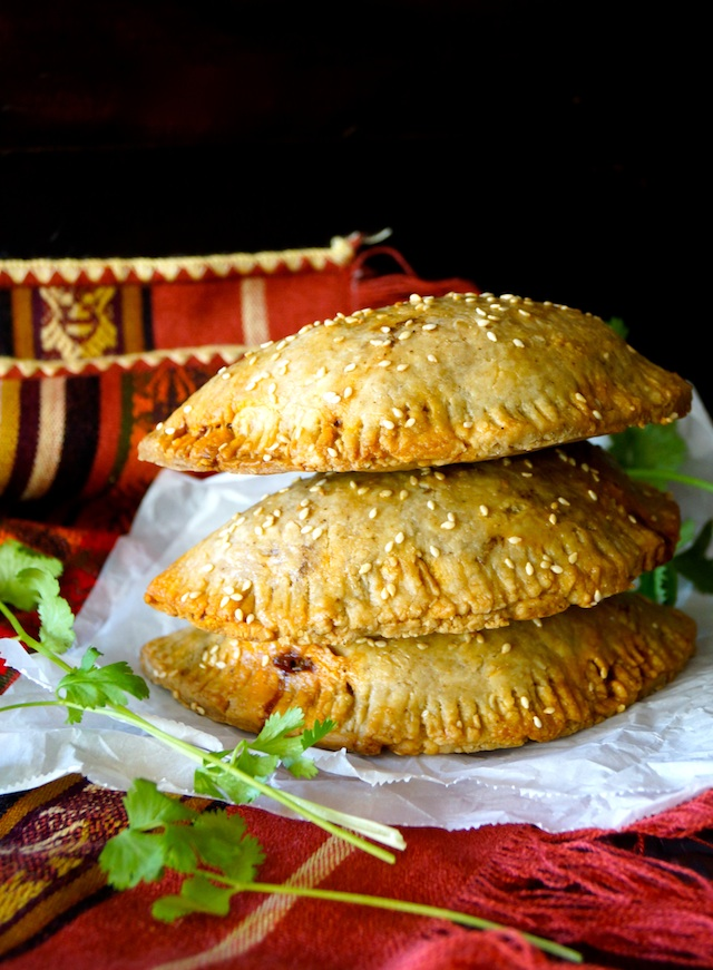 Stack of 3 Chorizo-Potato Spiced Sesame Hand Pies on parchment paper with fresh cilantro.