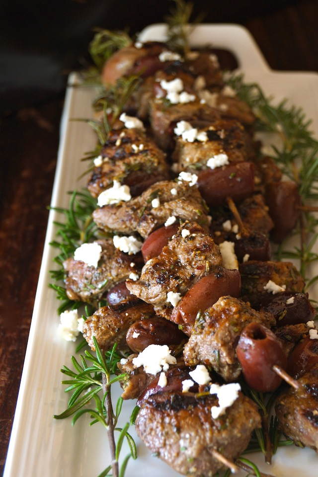 Rosemary Lamb Skewers sprinkled with fresh white Feta cheese crumbles on a narrow what platter.