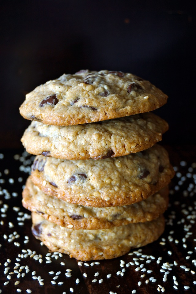 4 Sesame Chocolate Chip Cookies stacked with a black background with sprinkled sesame seeds.