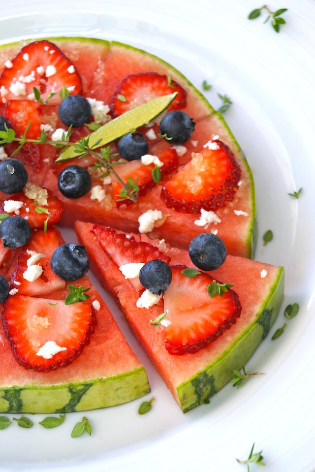 Sliced Watermelon Pizza Recipe with Lime, with one wedge slightly removed, with fresh blueberries, strawberries and thyme.