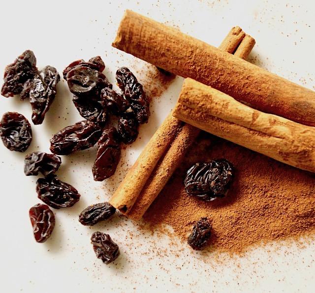 cinnamon sticks, ground cinnamon and raisins on white plate