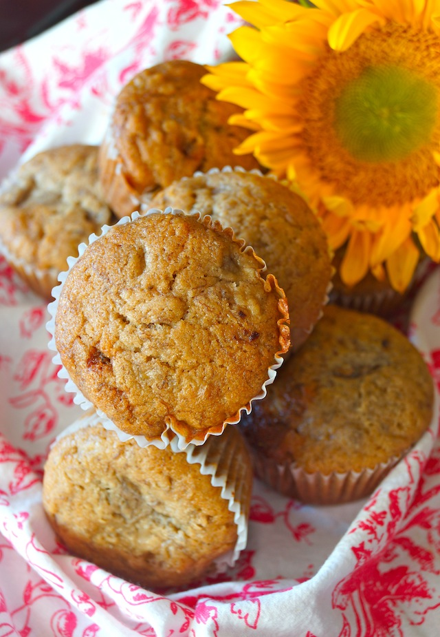 Honey Spiced Banana Muffins with a bright yellow sunflower with a pink and white cloth.