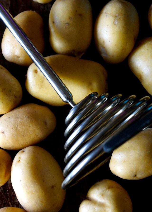 Raw Dutch Yellow Potatoes and a Smood potato smasher on a baking sheet.