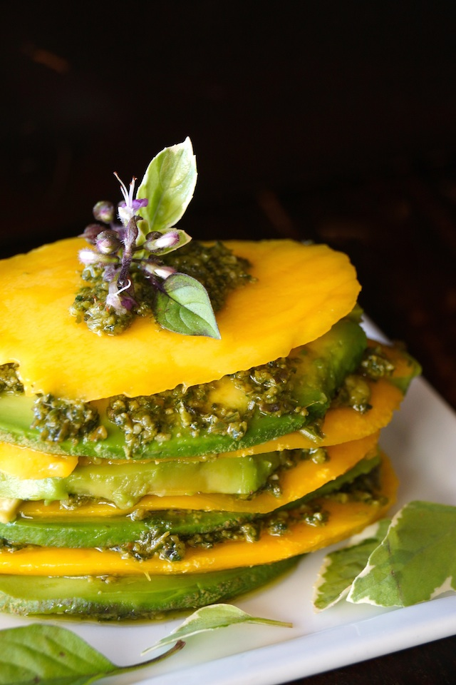 Mango Avocado Pesto Stack Recipe on a white plate with a purple basil flower on top.