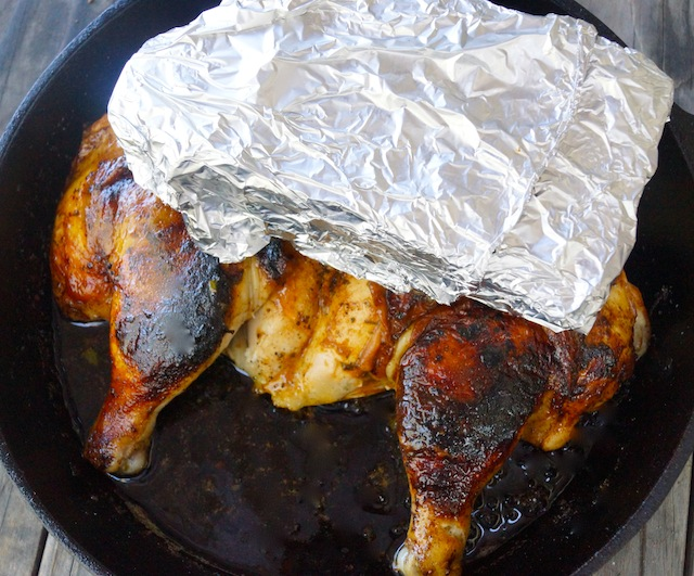 Roasted Smoky Paprika Lemon Herb Chicken Under a brick wrapped in foil