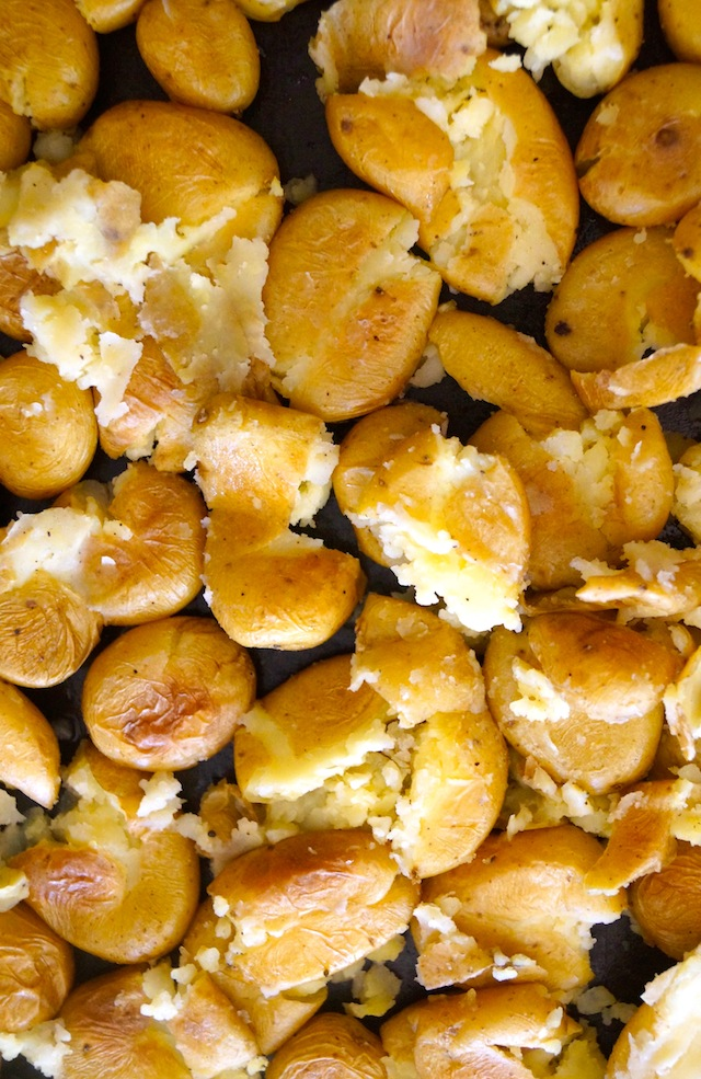 Baby Dutch Yellow Potatoes smashed on a bking sheet.