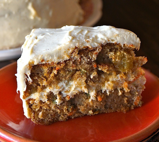 One slice of gluten-free Spiced Carrot Cake with Cardamom Cream Cheese Frosting on a red plate
