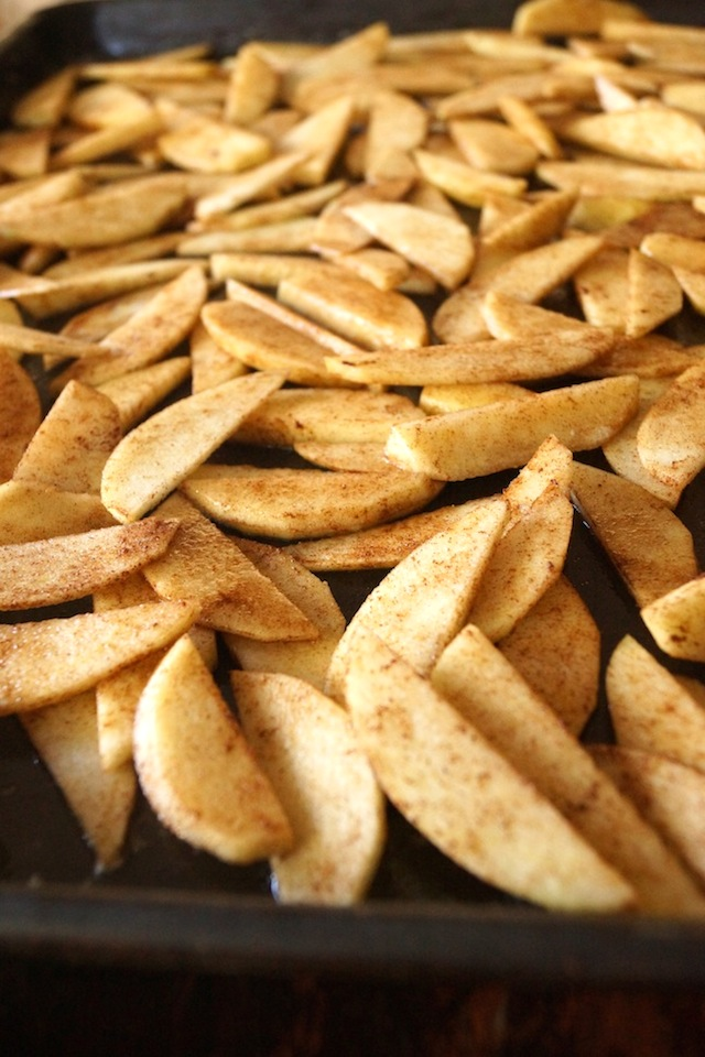 Sheet pan full of thinly sliced apples, with cinnamon and other spices sprinkled on top.