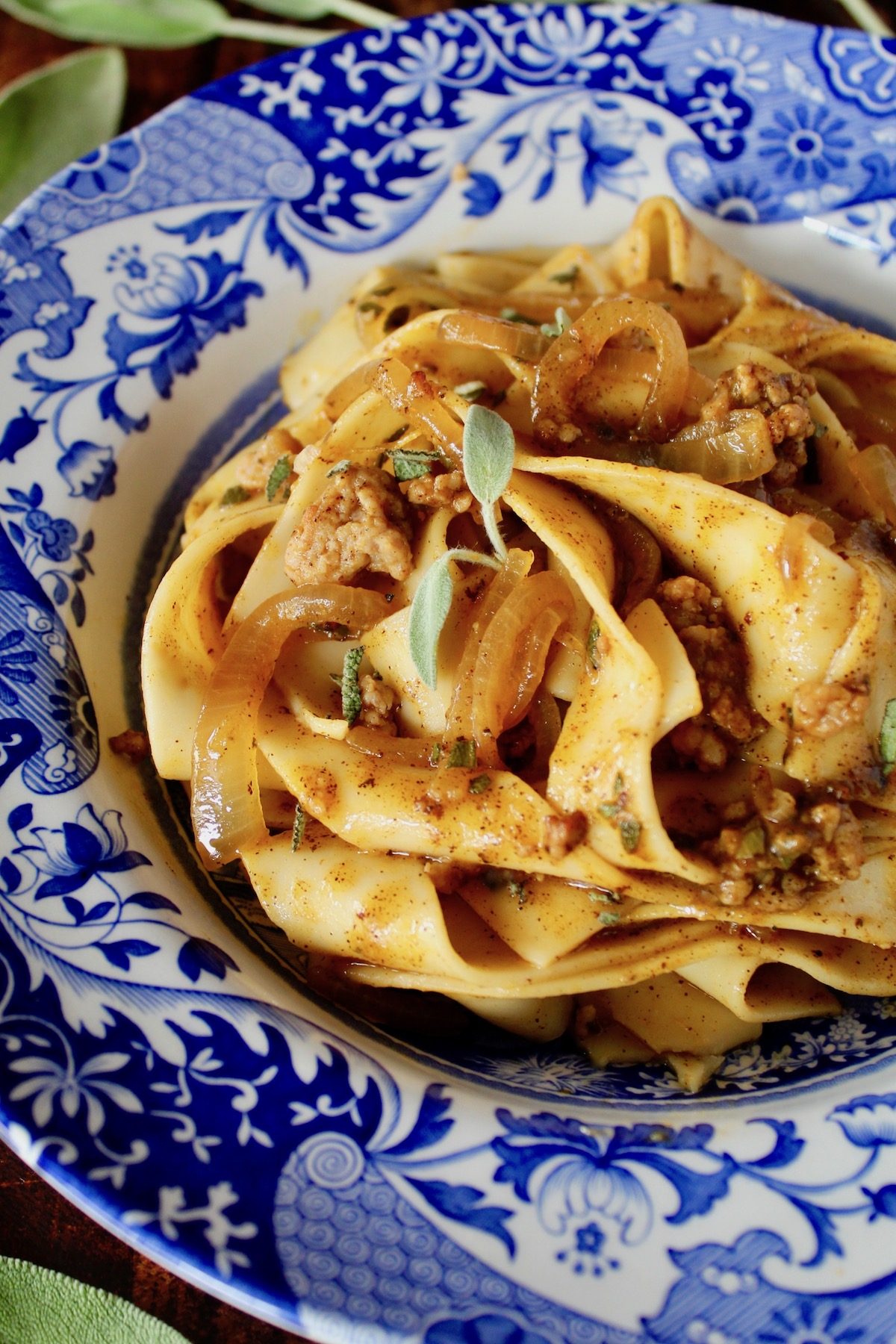 Pumpkin Pasta with Sausage mixed into Pappardelle in a blue and white bowl