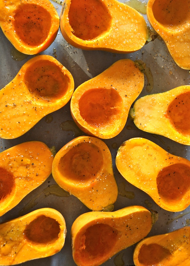 several honeynut squash, sliced in half on parchemnt, skin side down