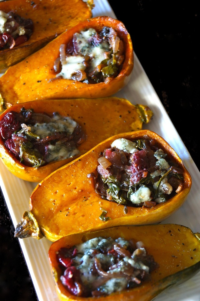 Caramelized Onion-Bacon and Cranberry Honeynut Squash - orange squash are cut in half and filled with cranberries, cheese, and onions