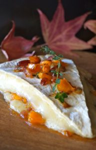 Cinnamon Persimmon Bacon Baked Brie Recipe melting on a cutting board