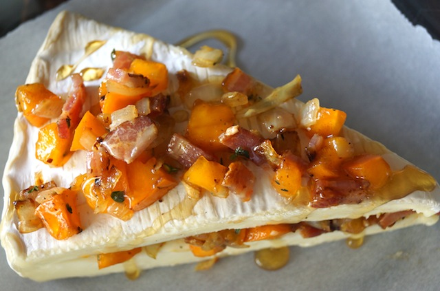 Cinnamon Persimmon Bacon diced on Brie wedge of brie, on parchment paper with drizzle of honey