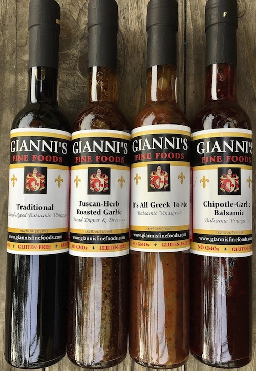 Giannis vinegars and dressings, four bottles lined up on a wooden surface.