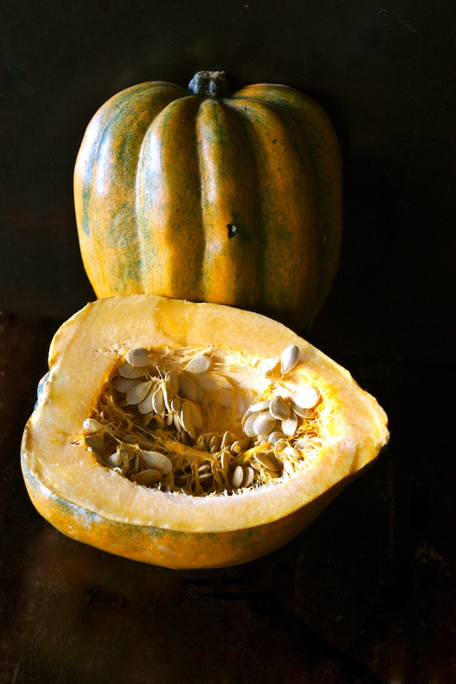 Golden-green-colored acorn squash split in half, with seeds still inside, with black background.