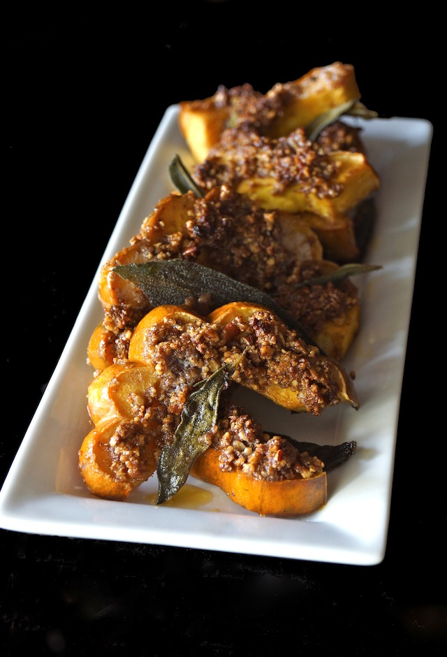 Roasted Pecan Crusted Acorn Squash with Crispy Sage Leaves -- This warmly spiced Pecan Crusted Acorn Squash with Crispy Sage Leaves is the ideal Thanksgiving side dish! It's full of delicious, comforting fall flavors, and it will be a beautiful addition to your holiday table.