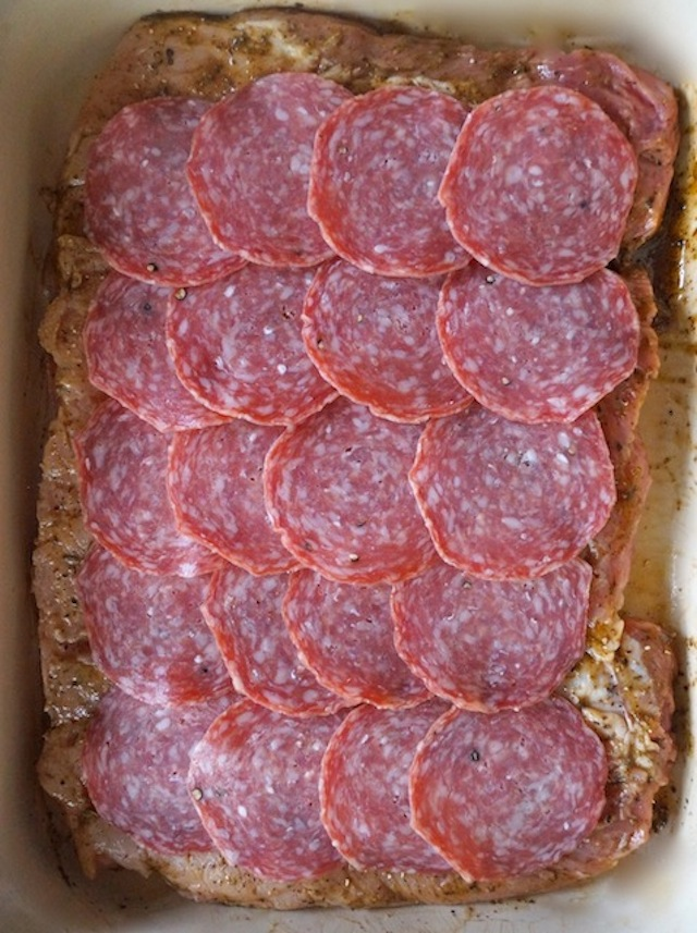 sliced salami in layers on top of butterflied pork loin