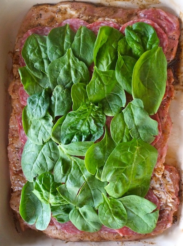 salami and spinach in layers on top of butterflied pork loin