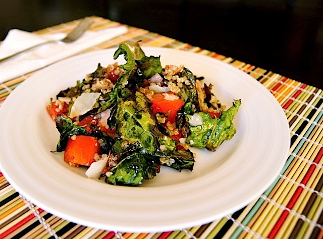 Roasted Kale Chip Quinoa Salad Recipe with Pancetta and Tomato Vinaigrette on a white plate on a striped-colored bamboo placemat.