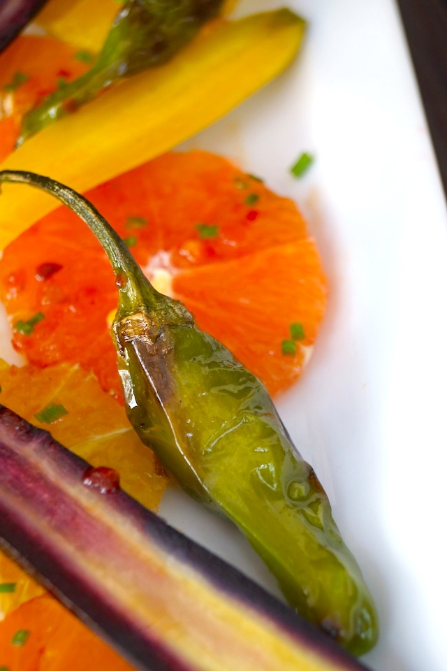 Close up of Colorful Citrus Carrot Salad Recipe with Shishito pepper on white plate.