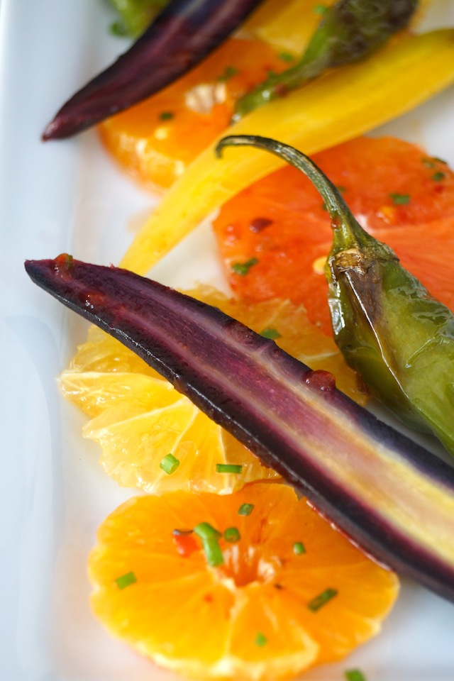 Close up of Colorful Citrus Carrot Salad Recipe on narrow, whtie plate.