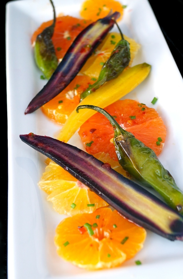 Colorful Citrus Carrot Salad with blistered shishito peppers on a white plate