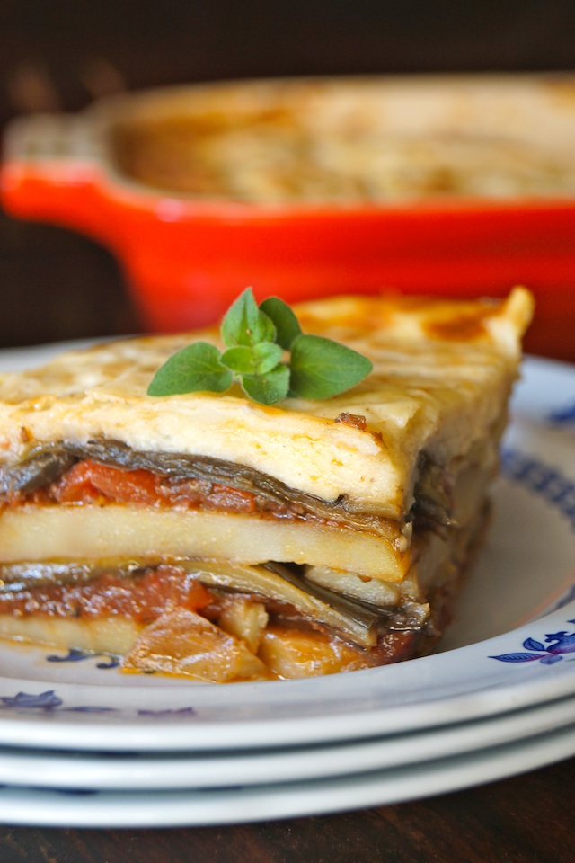 slice of Potato Moussaka on a small stack of plates, from Raghavan Iyer's newest cookbook, Smashed, Mashed, Boiled and Baked, this delicious, vegetarian Moussaka recipe is packed with warm spices, tender slices of potato and caramelized eggplant.