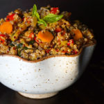 White curvy bowl almost overflowing with vegetable lemon quinoa