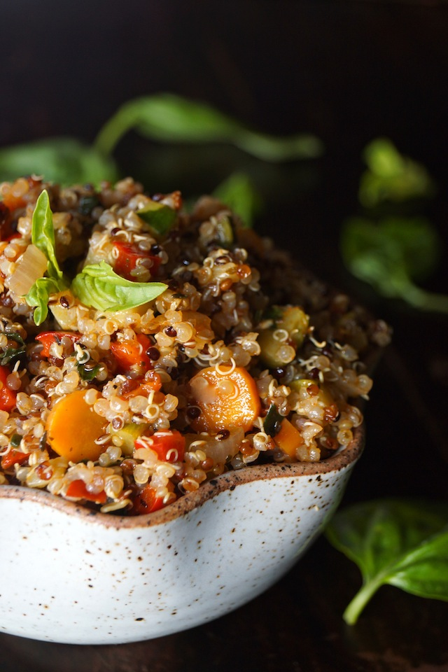 Smoky Lemon Vegetable Quinoa Recipe, with bright orange carrot round, red peppers and absil leaves on top