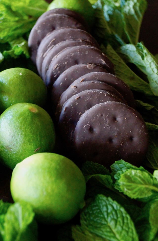 Three limes and a row of Thin Mint Girl Scout cookies surrounded by fresh mint leaves.