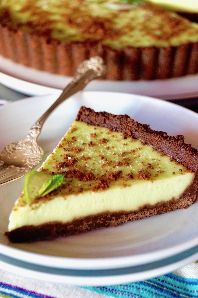 One slice of Thin Mint Key Lime Tart with whole tart behind it, on a white plate with a silver fork.