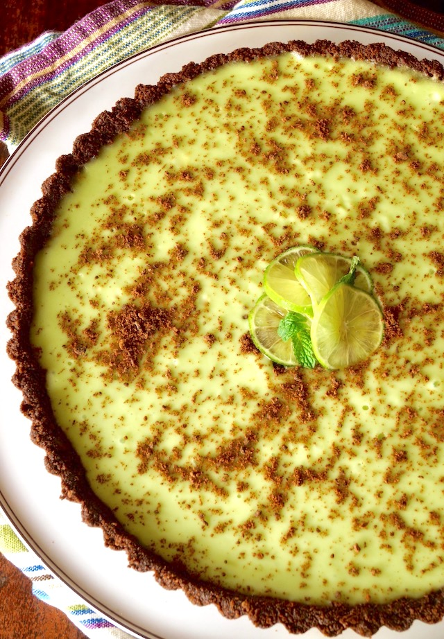 Thin Mint Key Lime Tart on a round, white platter with a striped cloth beneath it.