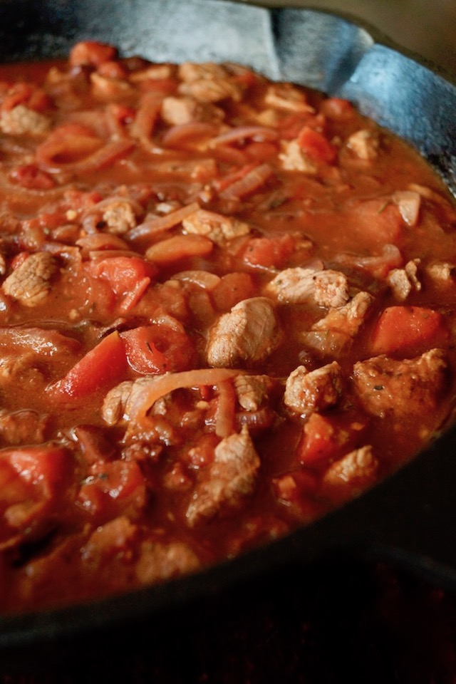 onions, tomatoes and the meat for Greek-Style Lamb Lasagna Recipe, in a large cast iron pan