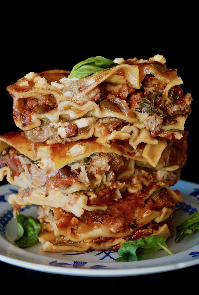 three big pieces of lamb Lasagna stacked on top one another with fresh basil leaves