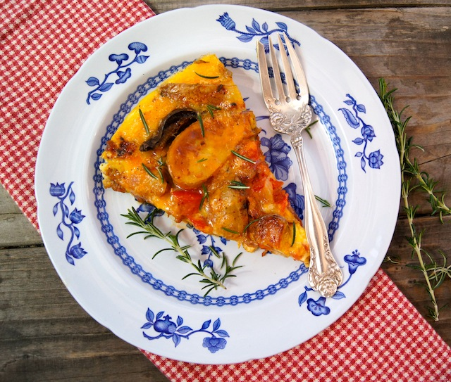 one slice of French Fry Frittata Recipe with Chipotle Chorizo Sauce on a white plate with blue flowers on the rim and a silver fork