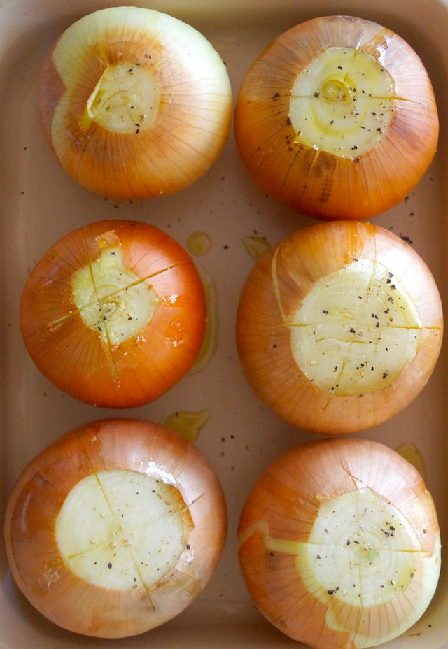 6 raw whole onions with tops cut off on a ceramic baking pan.