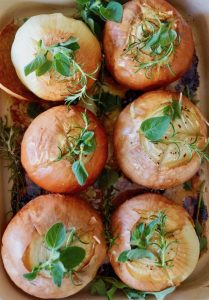 six whole roasted onions with fresh herbs in baking dish