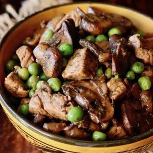 Mushrrom Pork Stew in an orange bowl with peas